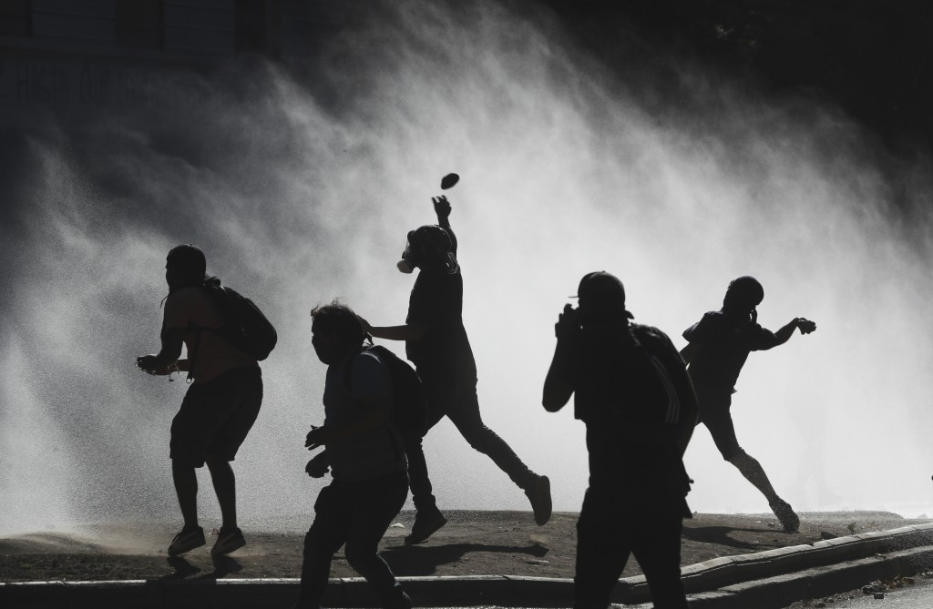 Anti-government demonstrators throw rocks at a police water cannon trying to disperse them in Santiago, Chile, Friday, Dec. 27, 2019. Chile has been r...