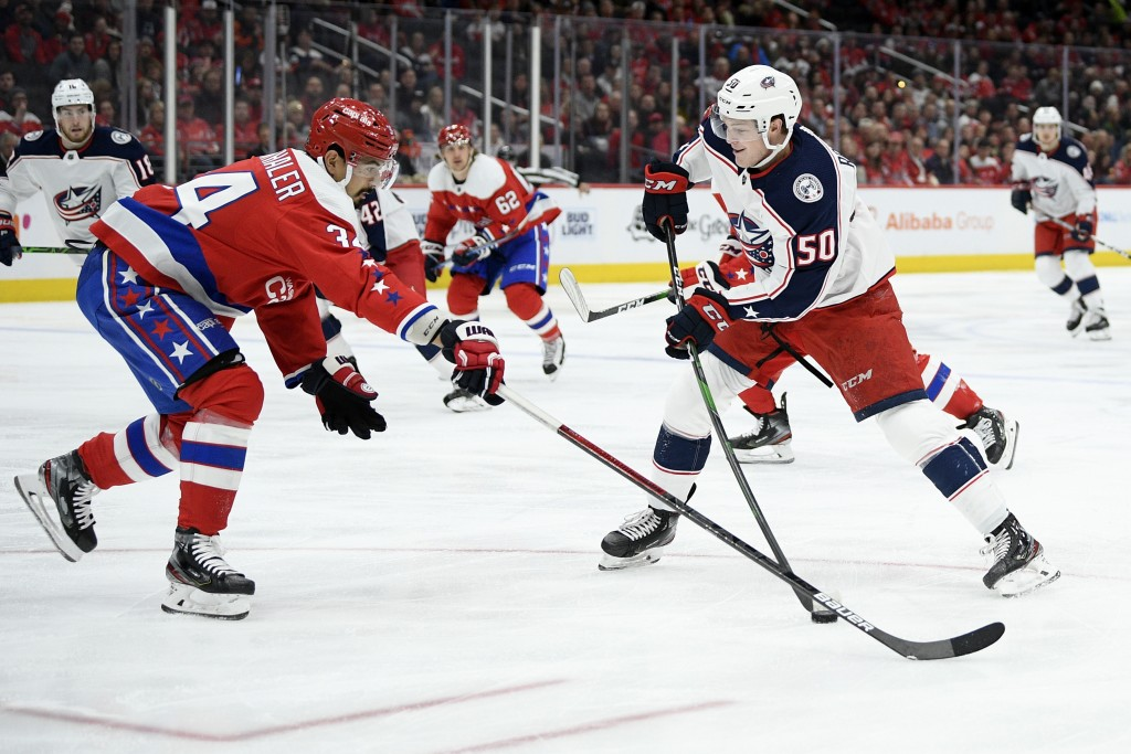 Columbus Blue Jackets left wing Eric Robinson (50) skates with the puck next to Washington Capitals defenseman Jonas Siegenthaler (34) during the firs...