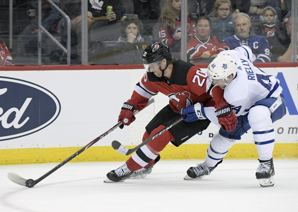 New Jersey Devils center Blake Coleman (20) controls the puck as he is checked by Toronto Maple Leafs defenseman Morgan Rielly (44) during the second ...