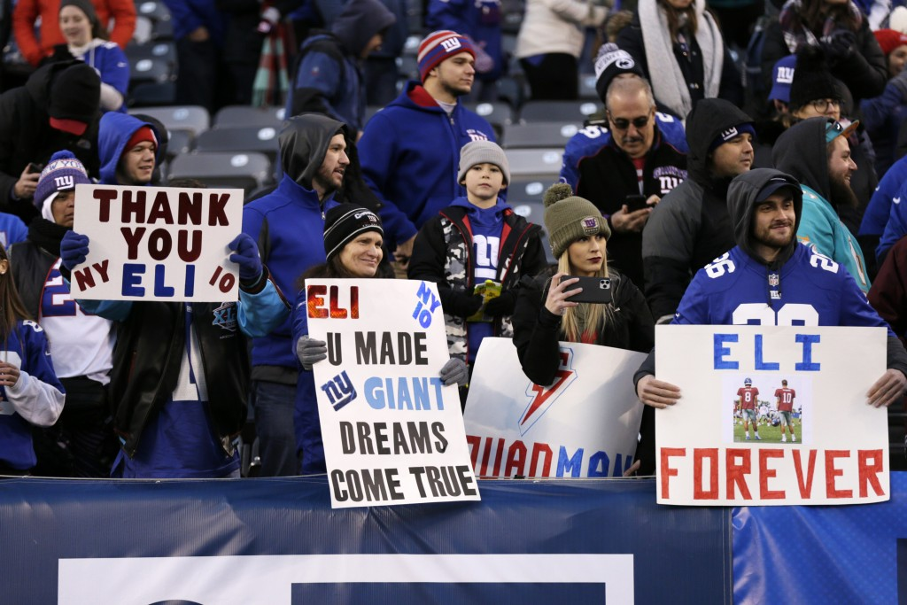 File-This Dec. 15, 2019, file photo shows New York Giants fans holding signs for Giants quarterback Eli Manning after an NFL football game against the...