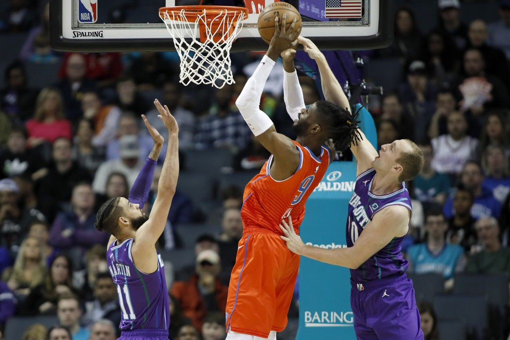 Oklahoma City Thunder's Nerlens Noel (9) tries to score between the defense of Charlotte Hornets' Cody Martin (11) and Cody Zeller during the first ha...