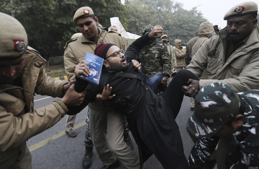 Police officers detain a protesting student, holding a book on the Indian constitution, outside Uttar Pradesh Bhawan during a protest against a new ci...