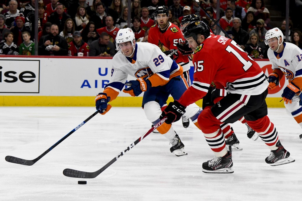Chicago Blackhawks center Zack Smith (15) moves the puck as New York Islanders center Brock Nelson (29) defends during the first period of an NHL hock...