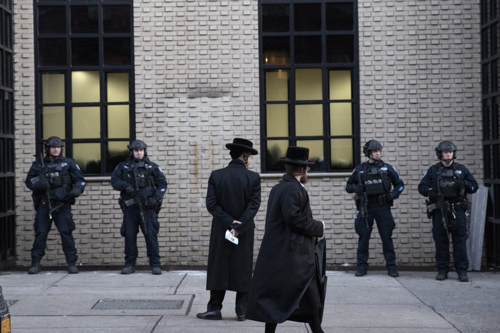 FILE - In this Dec. 11, 2019 file photo, Orthodox Jewish men pass New York City police guarding a Brooklyn synagogue prior to a funeral for Mosche Deu...