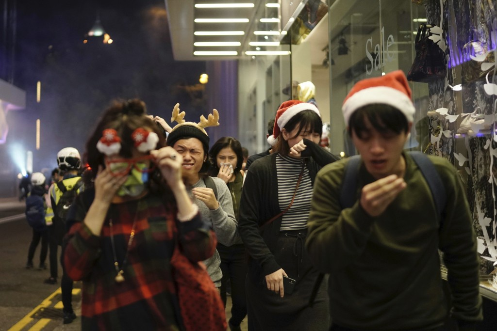 Residents dressed for Christmas festivities react to tear gas as police confront protesters on Christmas Eve in Hong Kong on Tuesday, Dec. 24, 2019. M...