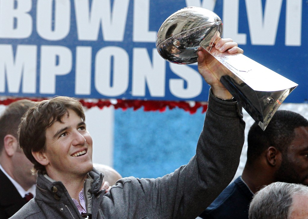 File-This Feb. 7, 2012, file photo shows New York Giants quarterback Eli Manning holding up the Vince Lombardi Trophy during the team's NFL football S...