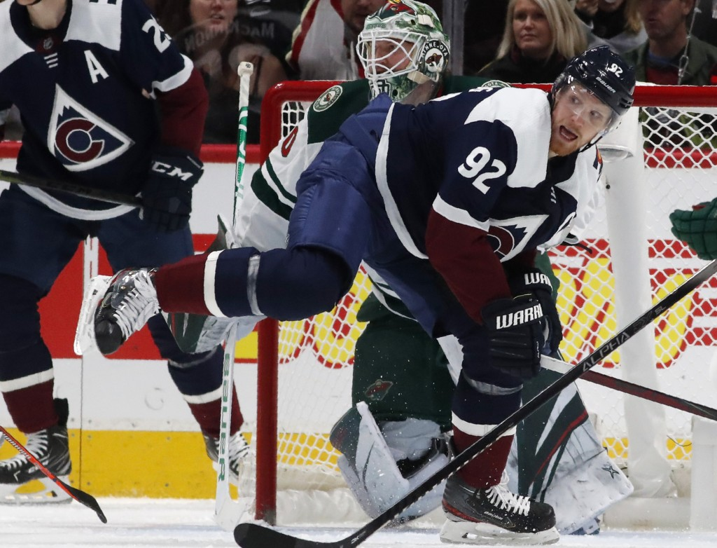 Colorado Avalanche left wing Gabriel Landeskog, front, struggles to stay on his skates as he looks for a pass while in front of Minnesota Wild goalten...