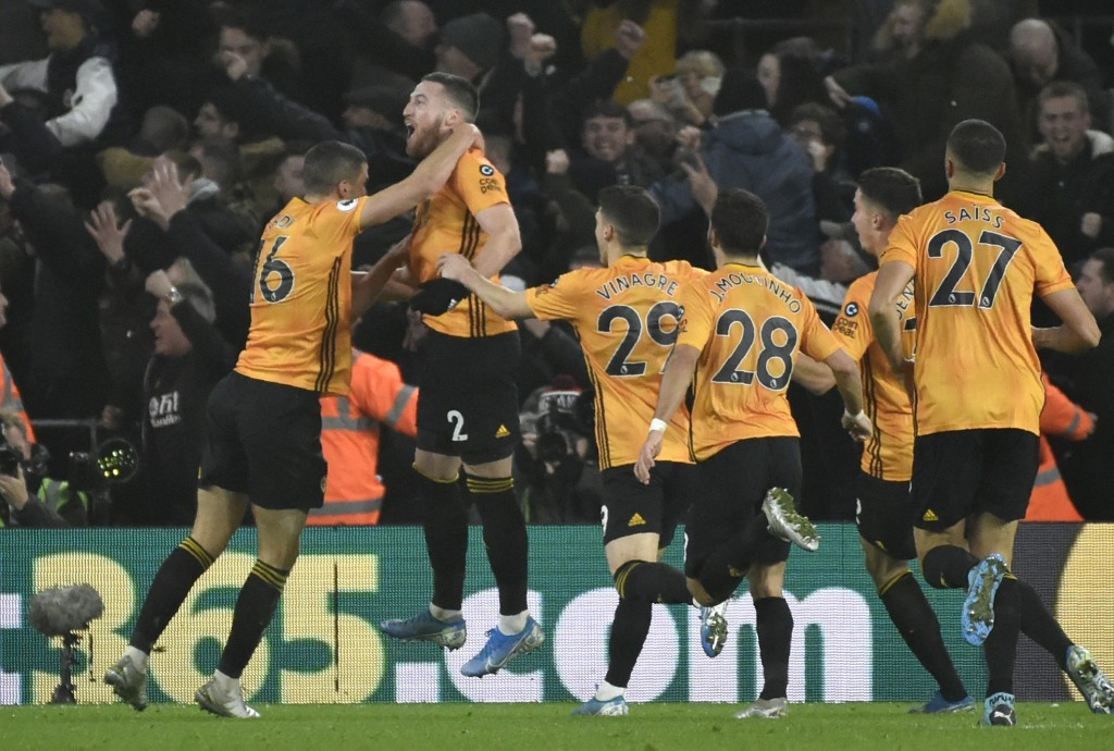 Wolverhampton Wanderers' Matt Doherty, jumps in celebrations with his teammates after scoring his side's third goal during the English Premier League ...