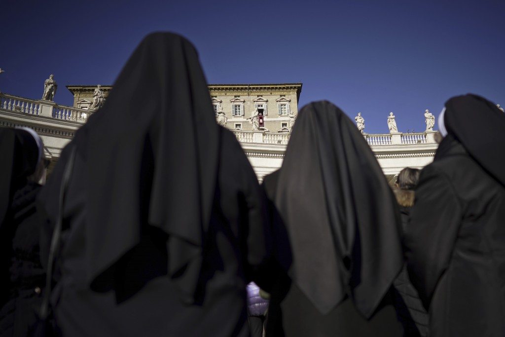 Nuns watch Pope Francis as he delivers his blessing during the Angelus noon prayer he recited from the window of his studio overlooking St. Peter's Sq...