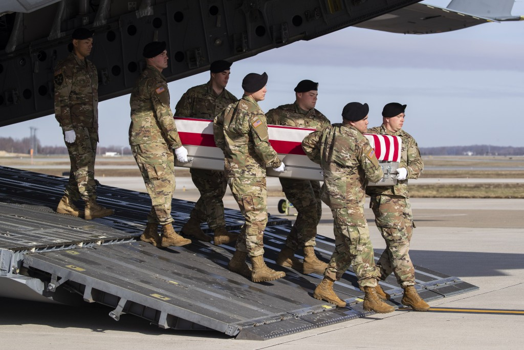 FILE - In this Dec. 25, 2019, file photo, an Army carry team moves a transfer case containing the remains of U.S. Army Sgt. 1st Class Michael Goble, a...