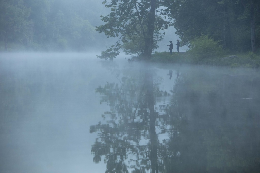 This July 26, 2019 photo provided by The Nature Conservancy shows two people fishing in the mist and fog over the Clinch River as seen from the Clinch...