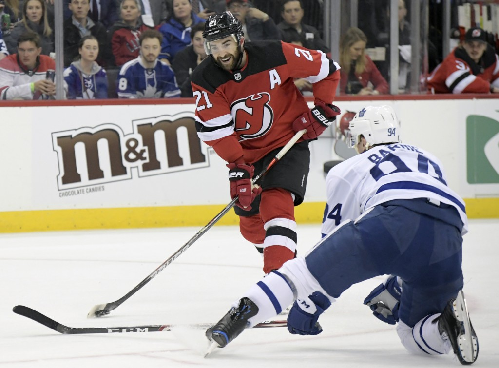 New Jersey Devils right wing Kyle Palmieri (21) shoots as Toronto Maple Leafs defenseman Tyson Barrie (94) defends during the second period of an NHL ...