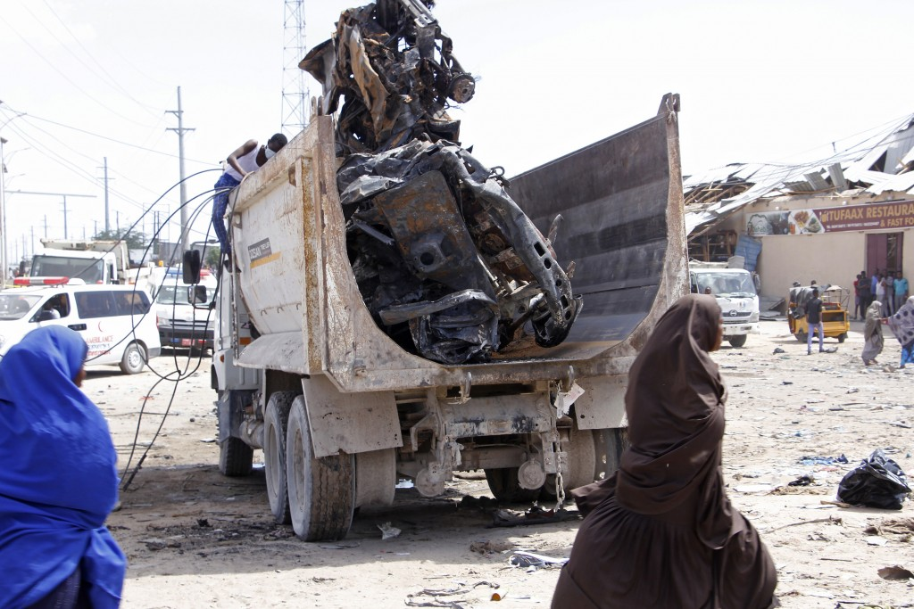 A truck carries wreckage of a car used in a car bomb in Mogadishu, Somalia, Saturday, Dec. 28, 2019. A truck bomb exploded at a busy security checkpoi...