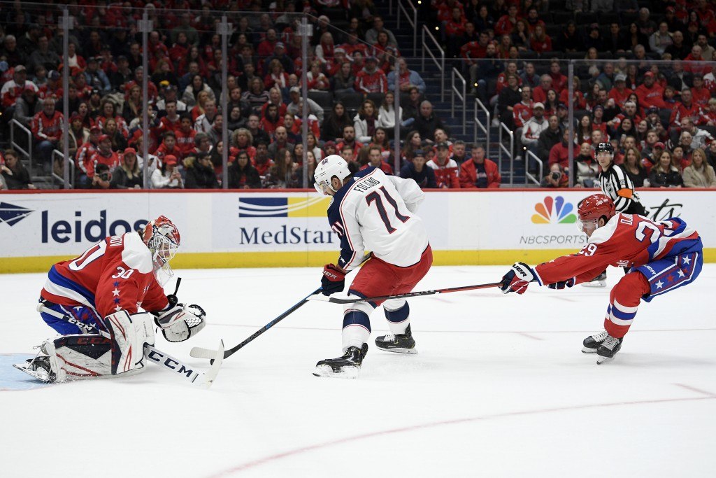Columbus Blue Jackets left wing Nick Foligno (71) skates with the puck between Washington Capitals goaltender Ilya Samsonov (30), of Russia, and defen...