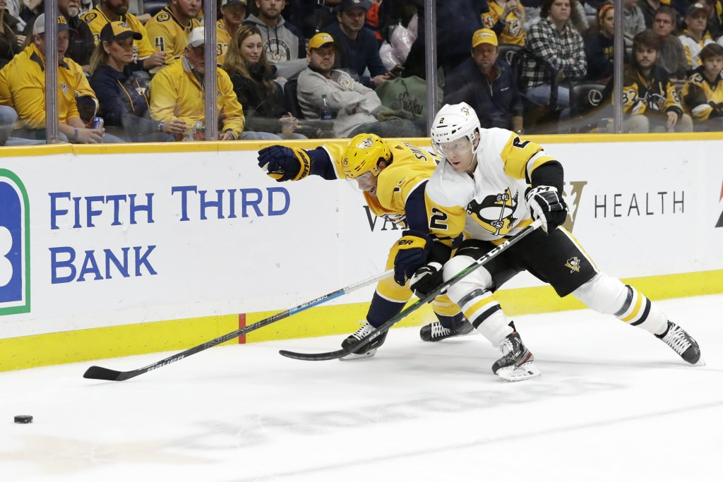 Pittsburgh Penguins defenseman Chad Ruhwedel (2) and Nashville Predators right wing Craig Smith (15) skate into the corner after the puck during the s...