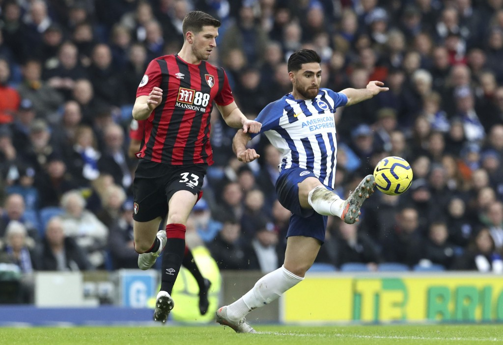 Bournemouth's Chris Mepham, left, and Brighton & Hove Albion's Alireza Jahanbakhsh battle for the ball during the English Premier League soccer match ...