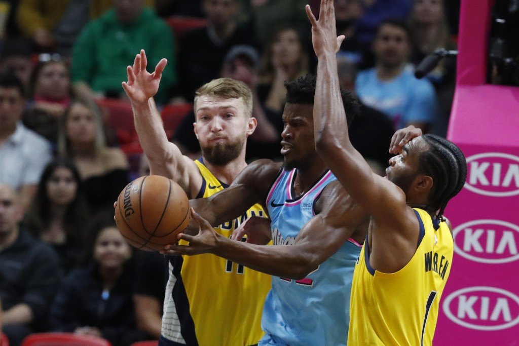 Miami Heat forward Jimmy Butler, center, loses control of the ball as he is guarded by Indiana Pacers forwards Domantas Sabonis, left, and T.J. Warren...