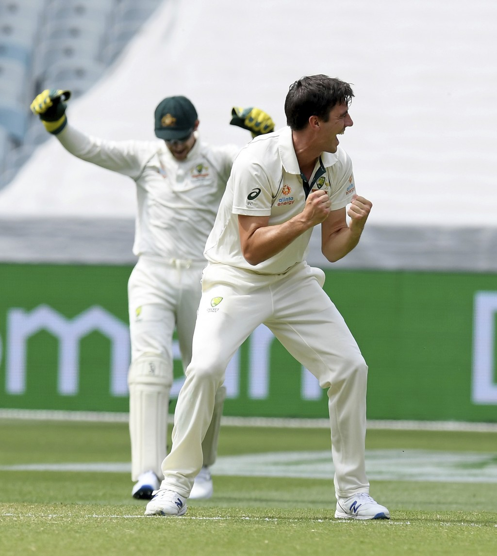 Australia's Pat Cummins, right celebrates the wicket of New Zealand's Henry Nicholls, left, during a cricket test match in Melbourne, Australia, Satur...