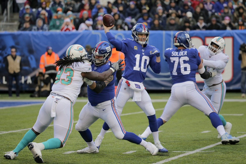 File-This Dec. 15, 2019, file photo shows New York Giants quarterback Eli Manning (10) passing against the Miami Dolphins during the second quarter of...