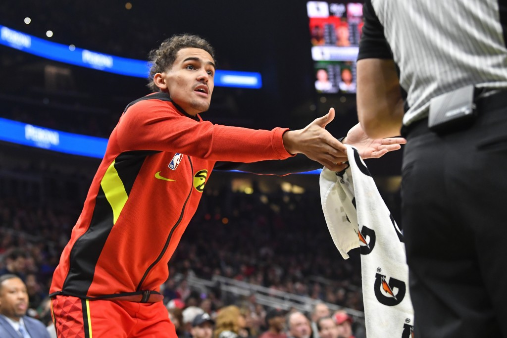 Atlanta Hawks guard Trae Young, left, pleads for a call from an official during the first half of an NBA basketball game against the Milwaukee Bucks, ...