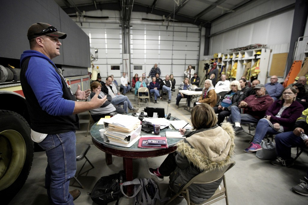 In this Oct. 24, 2019 photo, volunteer fire department chief and village trustee Zachary Klein briefs residents during a town hall meeting at the fire...