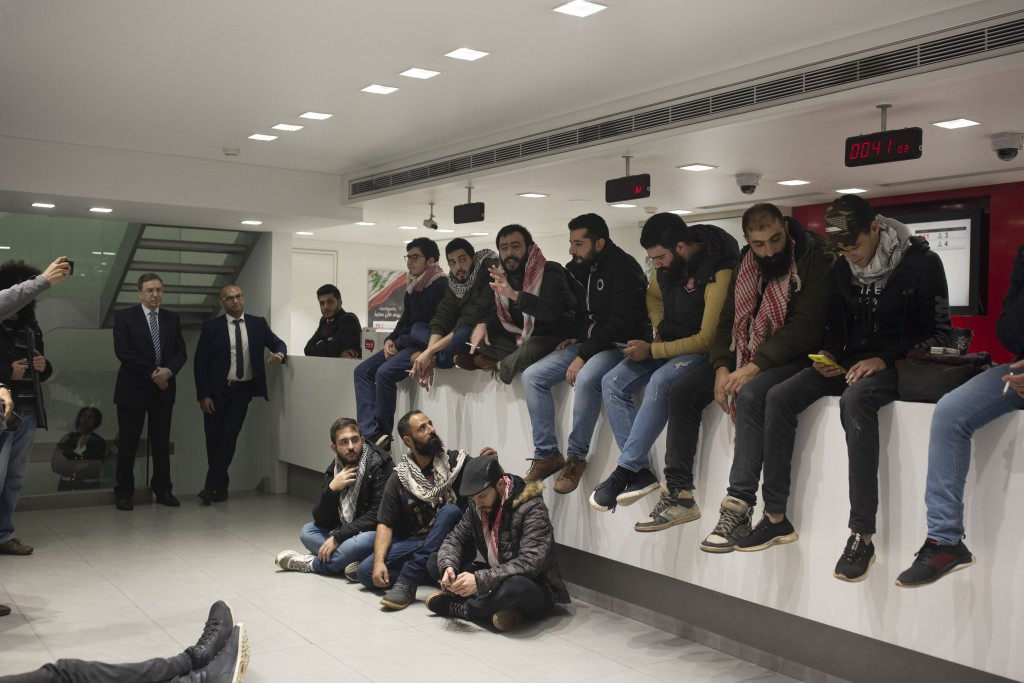 Anti-government protesters occupy the Hamra branch of BLC Bank Dec. 28, 2019 in Beirut, Lebanon. Banks have imposed weekly limits on withdrawals of U....