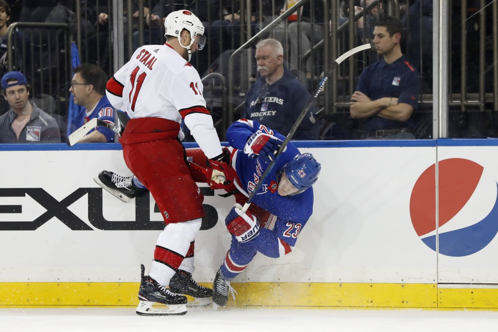 Carolina Hurricanes center Jordan Staal (11) checks New York Rangers defenseman Adam Fox (23), sending Fox to the ice during the first period of an NH...