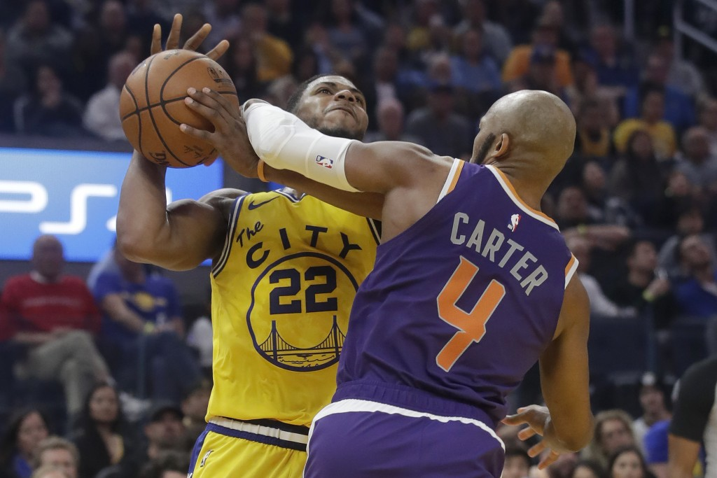 Golden State Warriors forward Glenn Robinson III (22) is fouled by Phoenix Suns guard Jevon Carter (4) during the first half of an NBA basketball game...