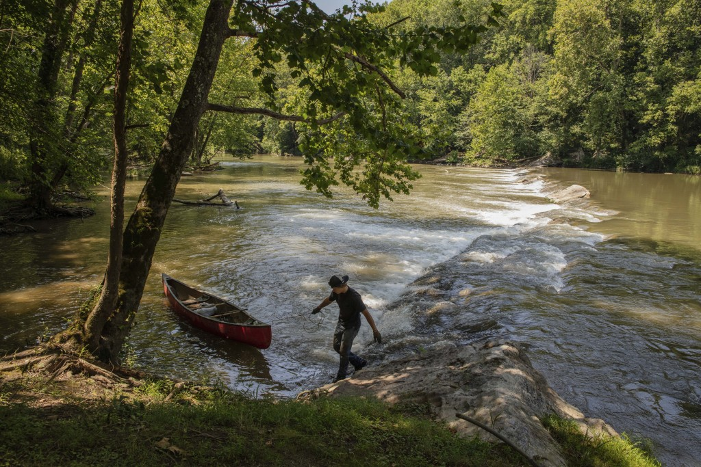 This July 26, 2019 photo provided by the Nature conservancy shows a StreamSweepers employee pulls a canoe to shore on the Clinch River, Va. The Cumber...