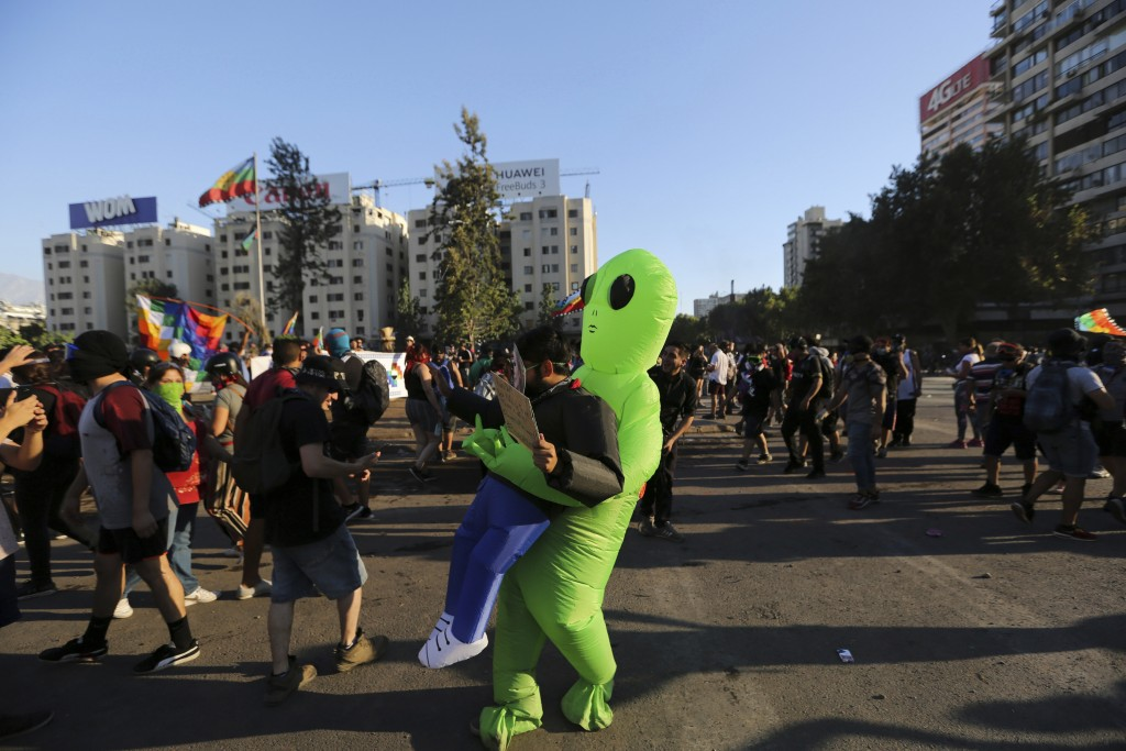 A Chilean anti-government demonstrator wears an alien costume during a protest in Santiago, Chile, Friday, Dec. 27, 2019. Chile has been roiled by con...