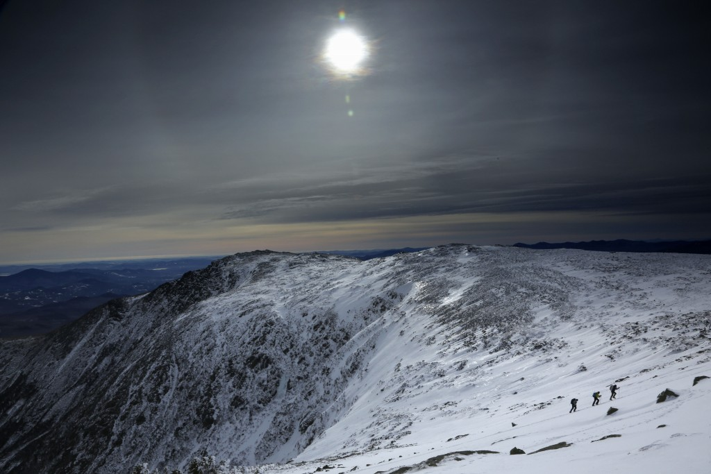 Under a midday winter solstice sun, a trio of climbers make their way up a slope on Mount Washington, Saturday, Dec. 21, 2019, in New Hampshire. Neith...