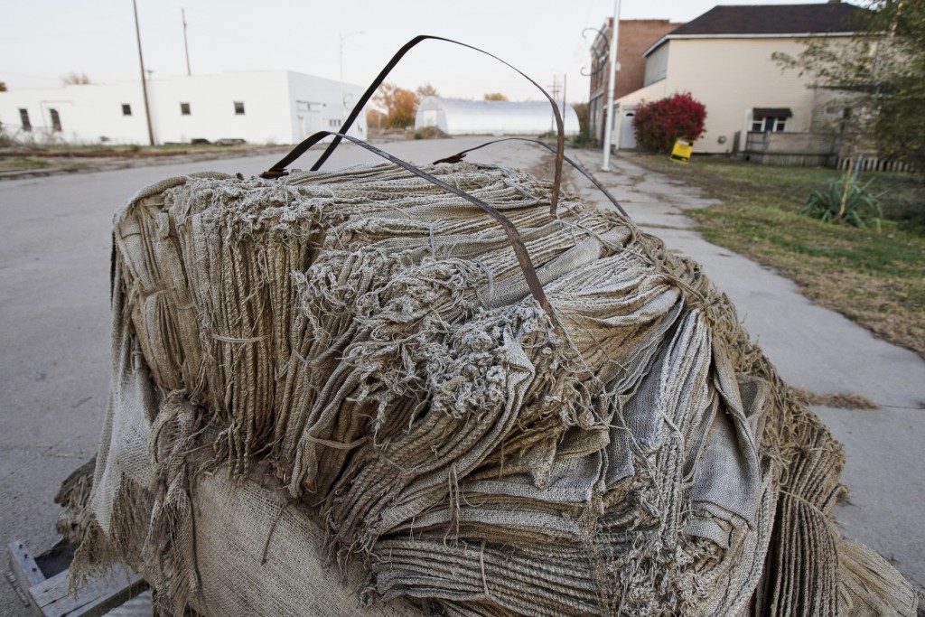 In this Oct. 24, 2019 photo, burlap bags for sandbagging remain on a street following flooding in Winslow, Neb. It took only minutes for swift-moving ...