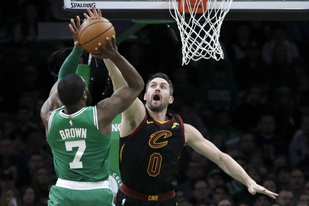 Boston Celtics guard Jaylen Brown (7) shoots against Cleveland Cavaliers forward Kevin Love (0) in the first half of an NBA basketball game, Friday, D...