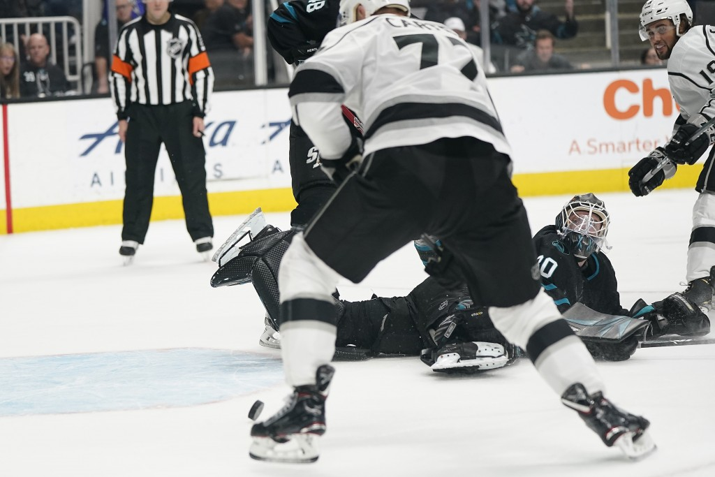 San Jose Sharks goaltender Aaron Dell (30) looks back as Los Angeles Kings center Jeff Carter (77) scores in overtime in an NHL hockey game in San Jos...