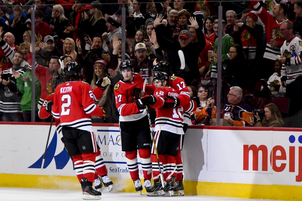 Chicago Blackhawks left wing Alex DeBrincat (12) celebrates with teammates after scoring a goal against the New York Islanders during the first period...