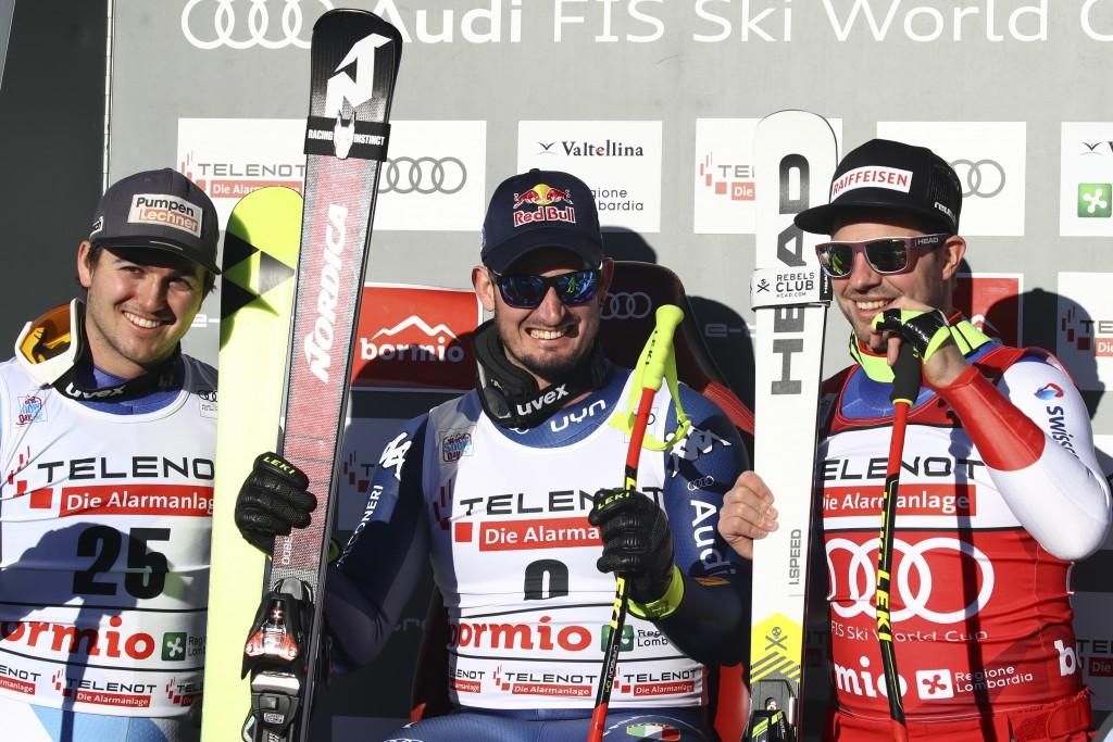 Italy's Dominik Paris, center, sits with Switzerland's Urs Kryenbuehl, left, and Switzerland's Beat Feuz at the finish area of an alpine ski, men's Wo...