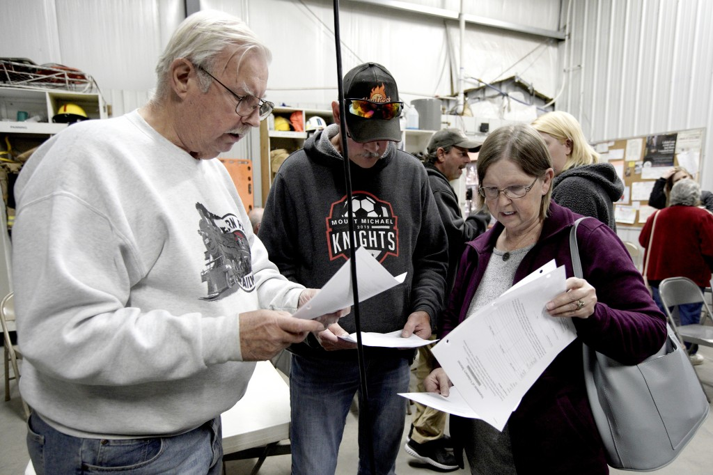 In this Oct. 24, 2019 photo, Richard Apking, left, and Debbie Johnson, right, examine documents following a town hall meeting at the fire hall in Wins...