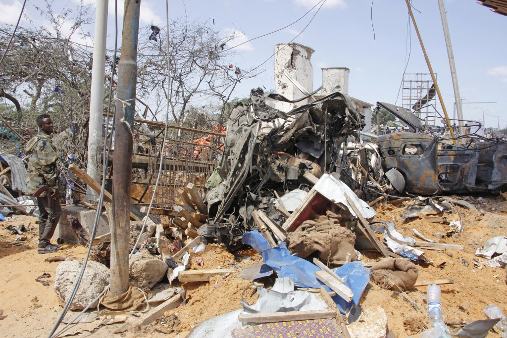 A soldier stands guard near wreckage of vehicles in Mogadishu after a car bomb in Mogadishu, Somalia, Saturday, Dec. 28, 2019. A truck bomb exploded a...