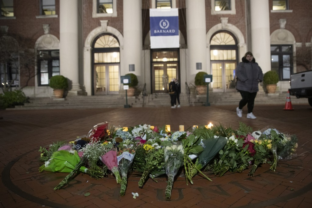 FILE - In this Dec. 12, 2019 file photo, a woman walks past a make-shift memorial for Tessa Majors inside the Barnard College campus in New York. Majo...