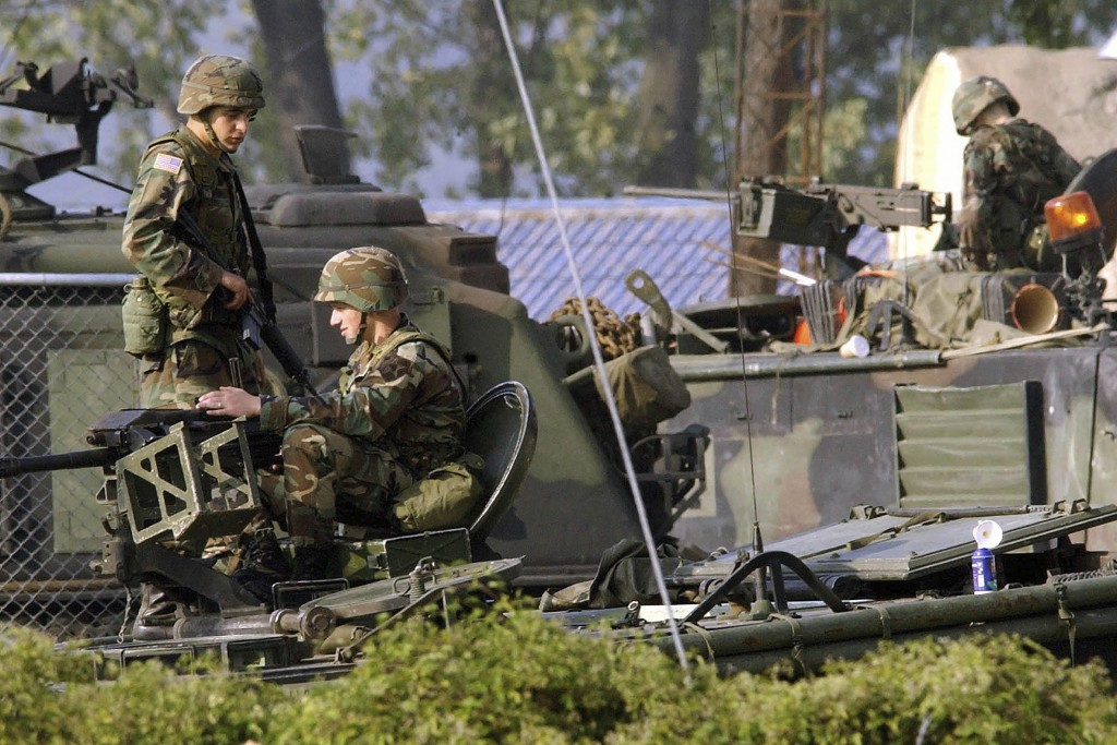 FILE - In this Oct. 6, 2004, file photo, U.S. Army soldiers stand guard on the armored vehicles at the their base in Dongducheon, South Korea. A U.S. ...