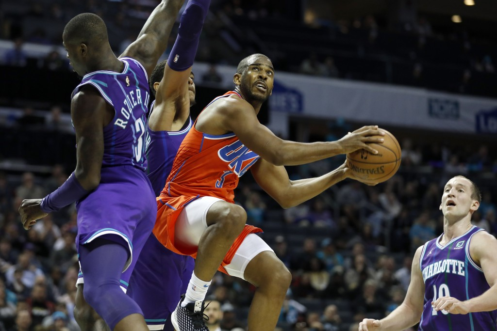 Oklahoma City Thunder's Chris Paul (3) looks for the basket as he flies by Charlotte Hornets' Terry Rozier (3) and P.J. Washington (25) during the sec...