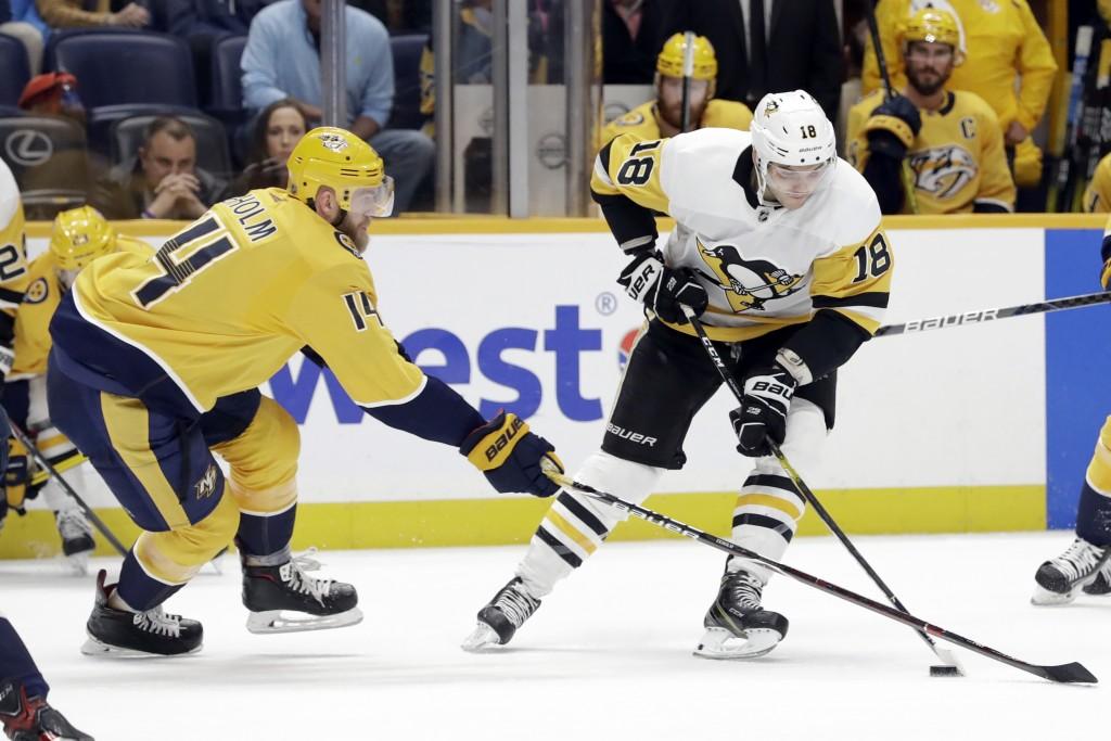 Nashville Predators defenseman Mattias Ekholm (14), of Sweden, tries to slow Pittsburgh Penguins center Alex Galchenyuk (18) during the first period o...
