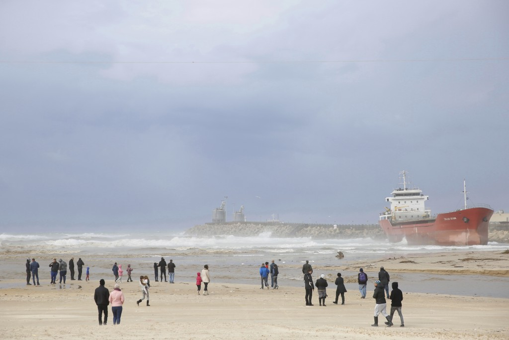 People look at the Zelek Star cargo ship carrying cement, stranded in the Mediterranean Sea beach in the southern Israeli port city of Ashdod, Friday,...