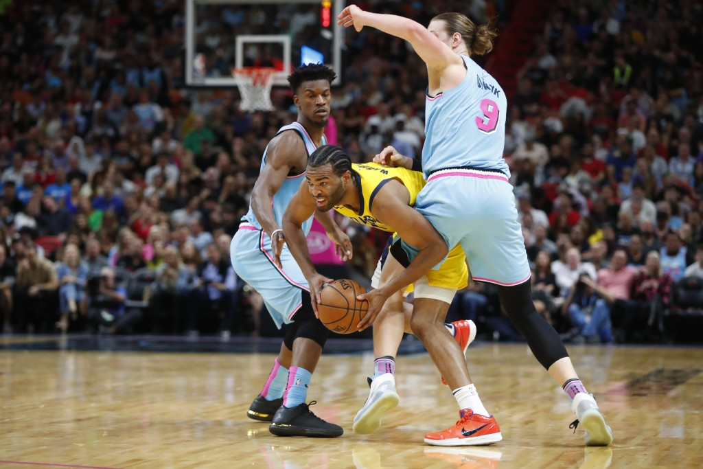 Indiana Pacers forward T.J. Warren, center, works between Miami Heat forward Jimmy Butler, left, and forward Kelly Olynyk during the first half of an ...