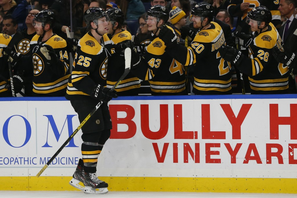 Boston Bruins defenseman Brandon Carlo (25) celebrates his goal during the third period of an NHL hockey game against the Buffalo Sabres, Friday, Dec....