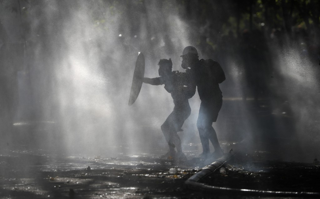 Anti-government demonstrators shield themselves amid the spray of a police water cannon trying to disperse them in Santiago, Chile, Friday, Dec. 27, 2...