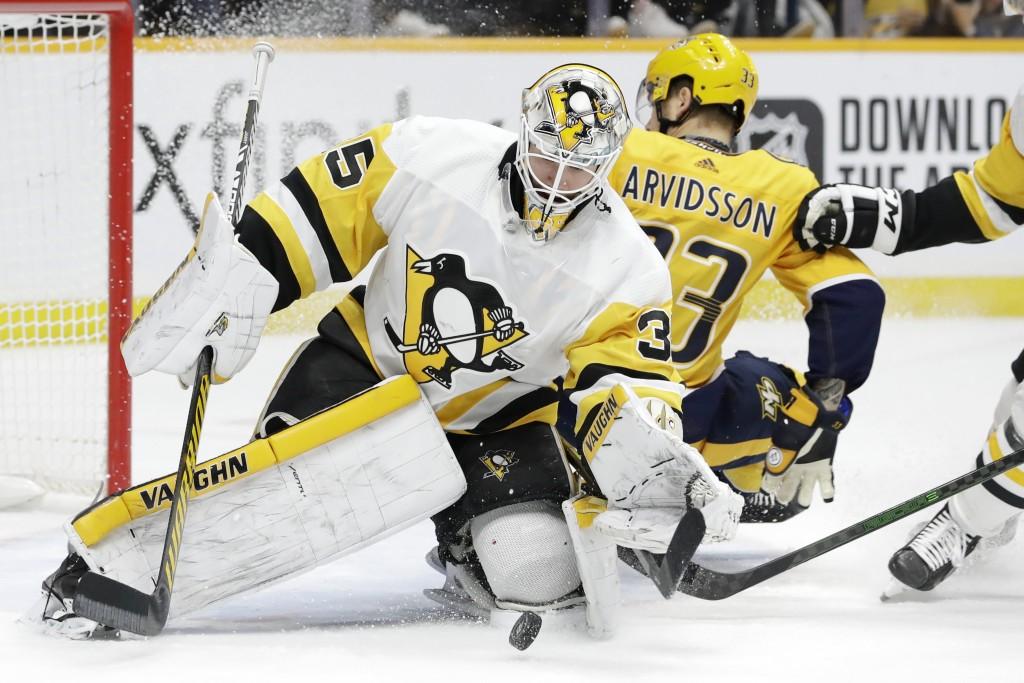Pittsburgh Penguins goaltender Tristan Jarry (35) grabs the puck as Nashville Predators right wing Viktor Arvidsson (33), of Sweden, slides by during ...