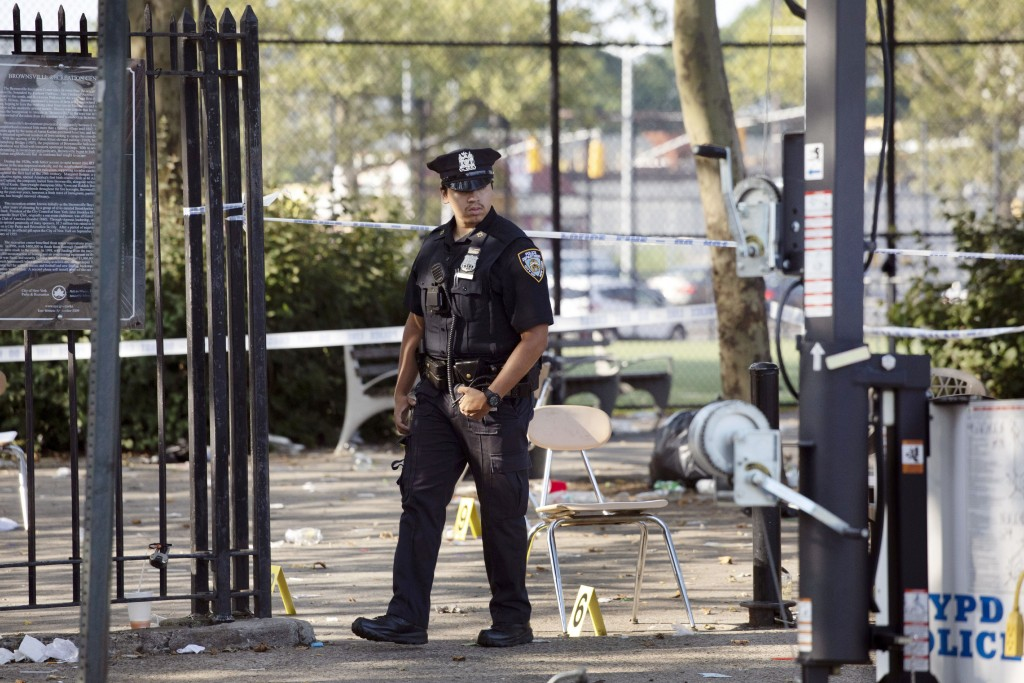 FILE - In this July 28, 2019 file photo, a police officer walks by yellow evidence markers at a playground after a shooting in the Brownsville neighbo...