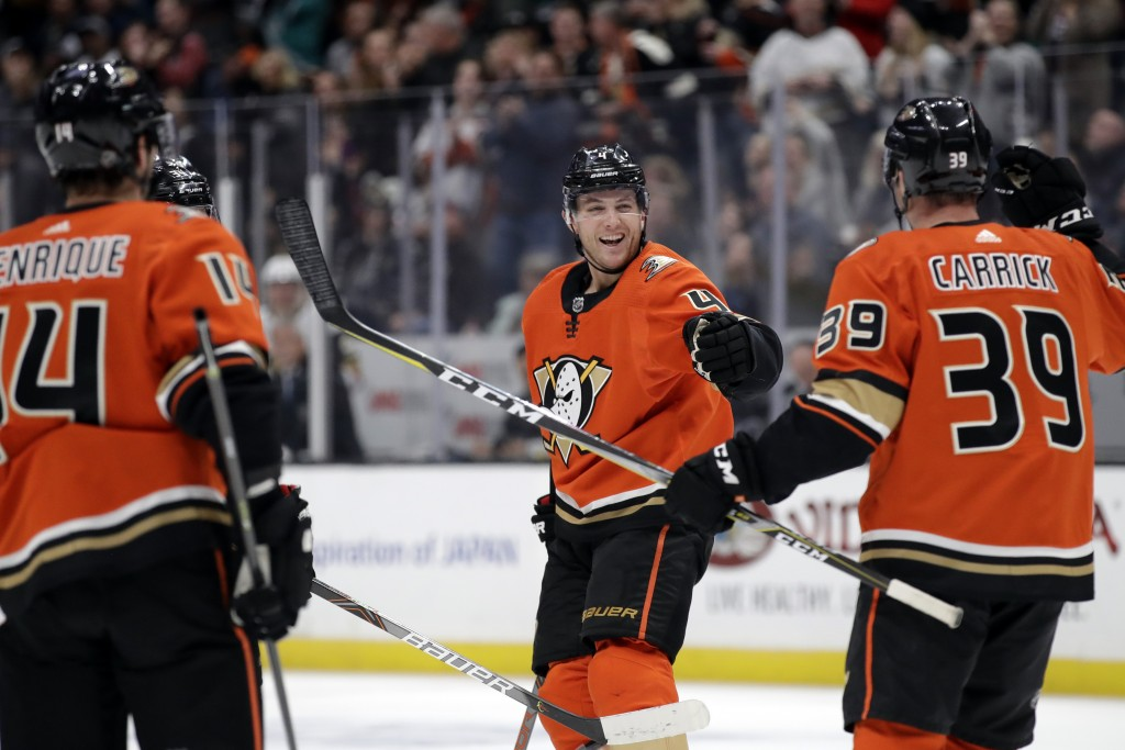 Anaheim Ducks' Cam Fowler, center, celebrates his goal with Adam Henrique, left, and Sam Carrick (39) during the second period of an NHL hockey game a...