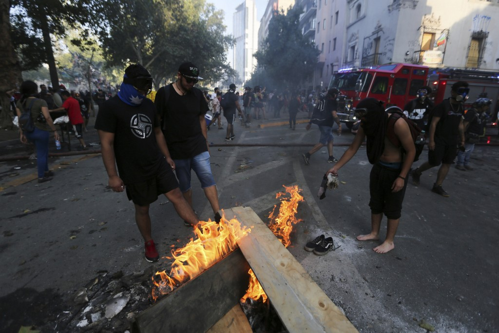 Chilean anti-government demonstrators dry their clothes in a fire after being sprayed by a police water cannon during a protest in Santiago, Chile, Fr...